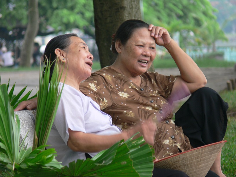 Two Vietnamese ladies sit on a park bench and catch up for a natter. after they finish their exercise one early morning on the side of Tay Ho Lake, Hanoi.
