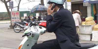 Vietnamese man wearing a suit talks on the phone while riding his motor bike.