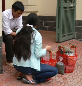 A women sells her Vietnamese Tea from 2 plastic baskets, going around selling door to door.