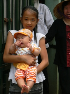 Vietnamese girl holds a screaming baby, which she is not phased by.