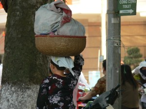 A Vietnamese lady carries a cane basket on her head, which contains hot bread. Fresh bread is baked in local bakeries and sold on the streets while its still hot ! Now that is what I call fresh !