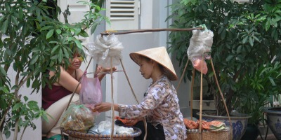 A Vietnamese lady sits on her door step and buys some ready-made food from a street vendor. You can't much more door to door service than this.