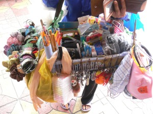 Vietnamese street vendor: My specialty store sells: hair bands, hair clips, hair ties, combs, mirrors, gloves, tissues, key rings, face masks, nail files, pens, ear pickers, lighters, notebooks, toothbrushes, scissors, combs, belts, razors, and wallets.