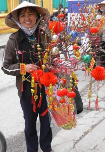 A Vietnamese street vendor has a beautiful red and gold display of Tet trinkets (lunar new year trinkets).
