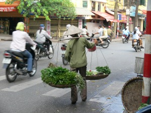 Vietnamese women street vendor walks down the street (pre 2007 helmet law) selling greens - check out the water bottle, she sprays the veges to keep them fresh.