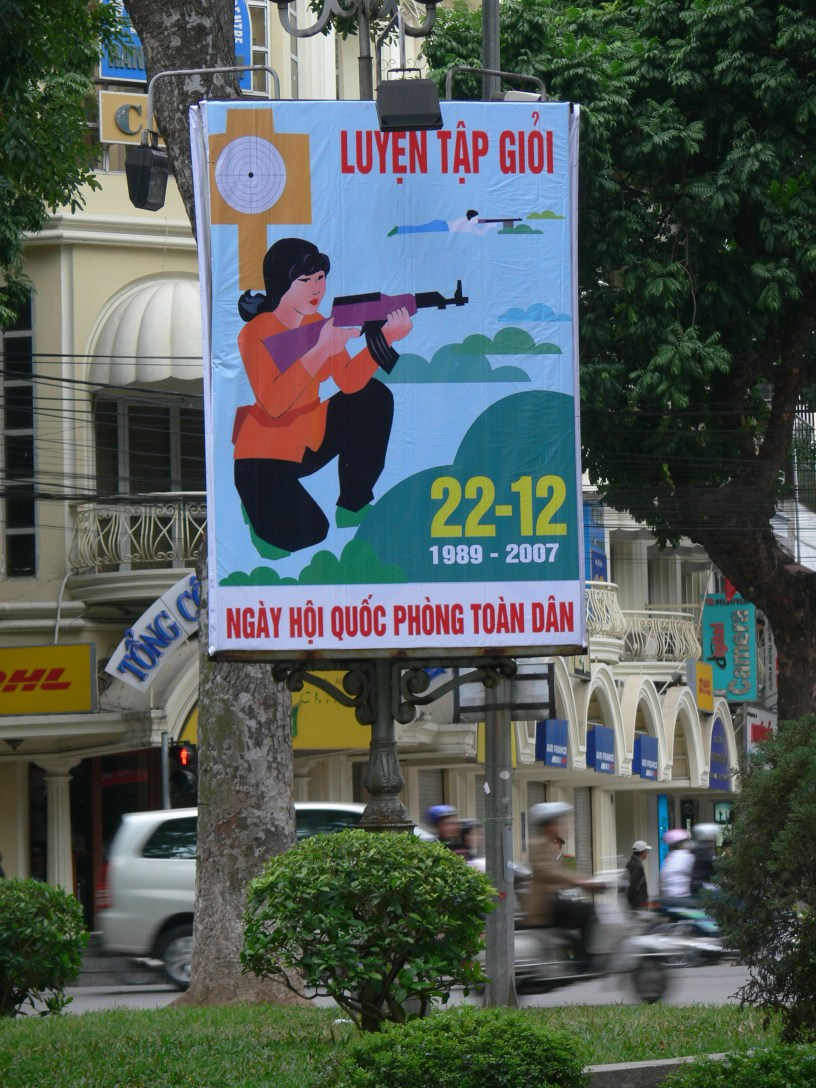 Public poster shows a woman holding a gun- 22 December, National Defense Day (People's Army of Vietnam Foundation Anniversary)