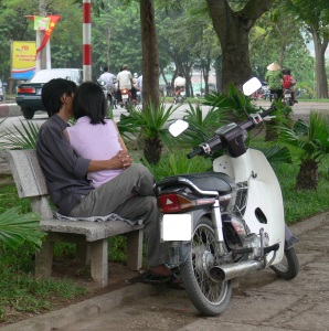 A Vietnamese couple cuddle up on a park bench, parked motorbike is beside them.
