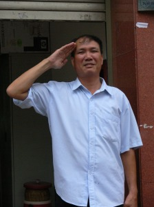 a man outside a building has fun with me by saluting me.