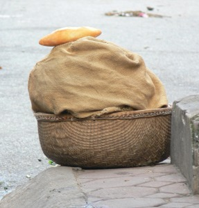 On Hanoi Streets, bread street sellers bread sits in a woven basket and to keep it warm they wrap it in clean sacking to keep it warm.