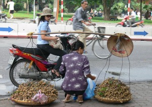 Drive In Vietnam style - lady on motorbike stops to buy fruit from a vendor on the footpath. Pre 2007 Helmet Law.