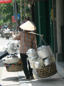 A Vietnamese street vendor carries a large display of goods to sell including: teapots, and pots and pans for every occasion.