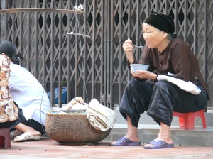 A Vietnamese older lady eats breakfast out of a bowl with contents made from a Street Vendor - I come here most days, it's convenient as just out my door way.