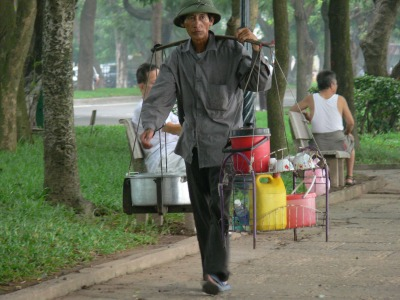Vietnamese male street vendor walks down the road - business is a bit slow down there, so I will try my luck up here.