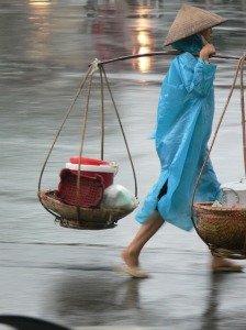 Vietnamese street vendor walking in the rain. Selling all day and now it's time to get home before it really thunders down.
