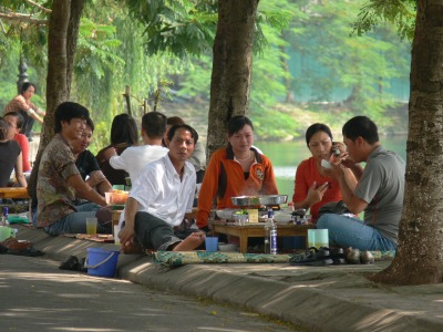 Groups of people sit around on mats with a small table and hotpot cooking on the table - Beautiful setting, under the trees at on a nice evening by Truc Bac Lake. Remember to take your shoes off before you walk on the mat.