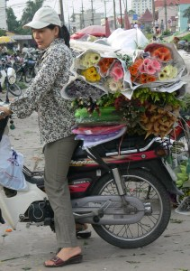 Florist heads back to her shop with her daily purchase laden on a bike with flowers and wrapping paper in Hanoi Flower Market or Cho Quảng An (pre 2007 helmet law).