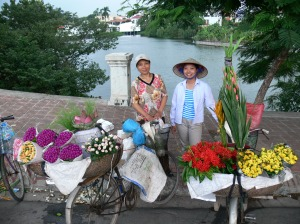 Hanoian Flower street vendors, like these ladies head to the market early to get their daily supplies. These ladies bike around town until all flowers are sold. Their bicycles with large cane baskets display the flowers in bunches and in buckets then at night they bike off home and come back the next day to do all over again. Often they have a spot they go to each day and have regular customers.