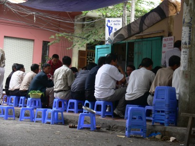 Men sitting eating lunch and more small blue plastic chairs stacked up waiting for more customers to arrive.