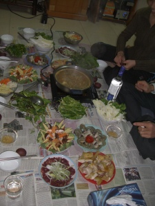 Home style steamboat with lots of delicious ingredients for a yummy feast. Newspaper is laid on the cleaned floor and then all different meats and vegetables nicely displayed on plates laid; plus a bottle of alcohol being opened.
