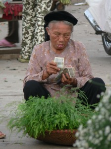 Counting today's takings, this older Vietnamese lady is counting today's takings, she only sells green foliage in Hanoi Flower Market or Cho Quan An..