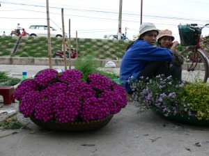 Two Vietnamese flower sellers look at me, with a look on their face asking . . . .Did you want buy something ?? in Hanoi Flower Market or Cho Quảng An.