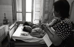 "Our Sympameal staff member chats ""It is sunny outside' to these patients as she visits them at their bed to give them meal coupons. Taken by Le Ngoc Anh."