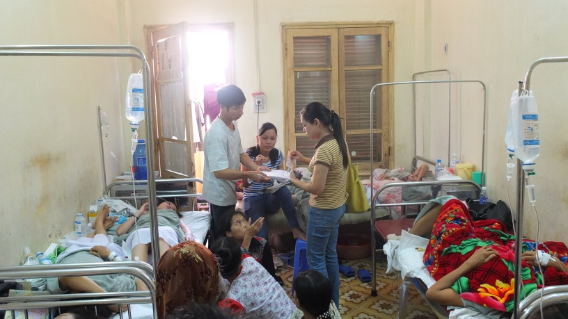 Sympameals staff in stripe yellow t-shirt deliver coupons to each patient in a chemotherapy ward. NOTE: 2 people per bed. Photo by Tran Minh Cuong,